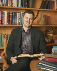 a brown-haired man sits in front of a bookcase with an open book on lap and stack of books in foreground